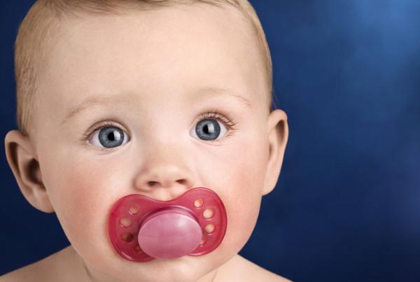 голубоглазый малыш с соской-пустышкой